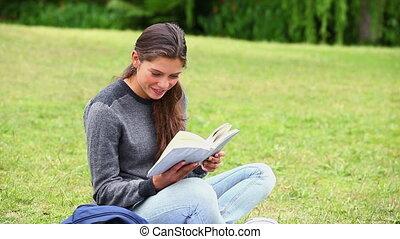 aandachtig, het boek van de lezing, het glimlachen, brunette