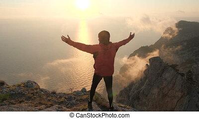 aanzicht, sunset., mooi, loonsverhogingen, staand, armen, zee, man, zijn, het genieten van, rand, hoog, schietende , apart, berg, back, gebaard, tracksuit