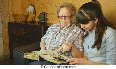 album, vrouw, oud, familie foto, nakomeling kijkend, sofa, thuis