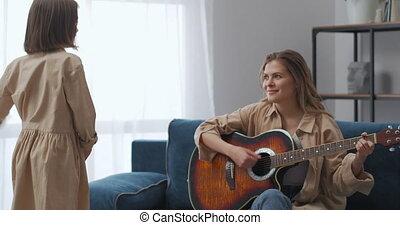 amusement, gezin, haar, thuis, weekend, spelend, meisje, gitaar, plezier, moeder, dancing, muziek, vrolijke , het luisteren, weinig; niet zo(veel)