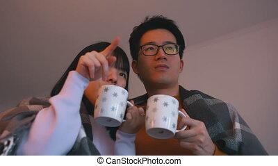 aziaat, schouwend, movie., paar, genegenheid, liefde, concept, hete thee, jonge, drinkt