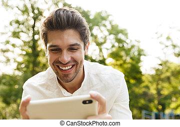 beeld, brunette, man, park, cellphone, jonge, het glimlachen, vasthouden