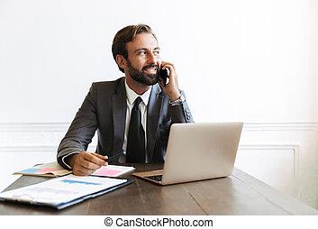 beeld, draagbare computer, klesten, terwijl, het glimlachen, kantoor, cellphone, werkende , zakenman, tevreden