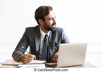 beeld, draagbare computer, terwijl, het glimlachen, kantoor, gebaard, werkende , het noteren, opmerkingen, zakenman