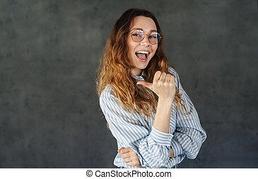 beeld, duim, vrouw, terzijde, gelukkig glimlachen, aantrekkelijk, wijzende