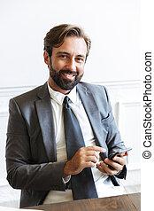 beeld, terwijl, het glimlachen, kantoor, cellphone, werkende , het kijken, tevreden, zakenman, het typen, fototoestel