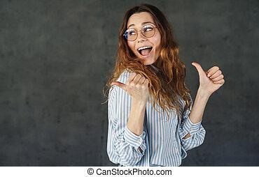 beeld, vrouw, terzijde, gelukkig glimlachen, aantrekkelijk, wijzende, duimen