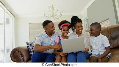 black , draagbare computer, thuis, comfortabel, aanzicht, bankstel, gebruik, 4k, jonge, voorkant, gezin, zittende