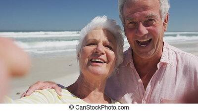 blazen, kaukasisch, kussen, senior, strand, verticaal, vrolijke , het kijken, fototoestel, paar