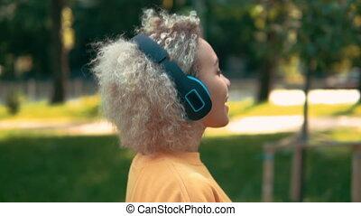 blonde, bovenkant, headphones, vrouw, buitenshuis, aanzicht