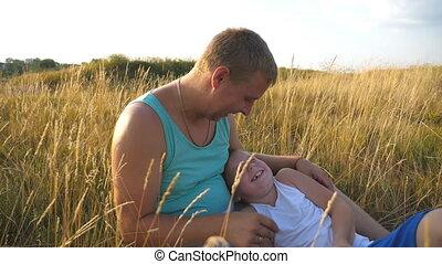 boy., zoon, vrolijk, afsluiten, weinig; niet zo(veel), vertragen, outdoor., vader, jonge, kieteldood, akker, vrolijke , zijn, kind, baby, man, papa, op, samen, hebben, motie, park., plezier, gras, spelend, het liggen