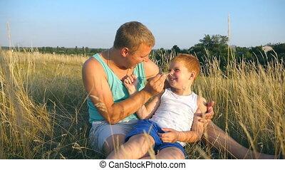 boy., zoon, vrolijk, afsluiten, weinig; niet zo(veel), vertragen, outdoor., vader, jonge, kieteldood, akker, vrolijke , zijn, kind, baby, man, gras, op, samen, spelend, motie, park., plezier, papa, hebben, het liggen