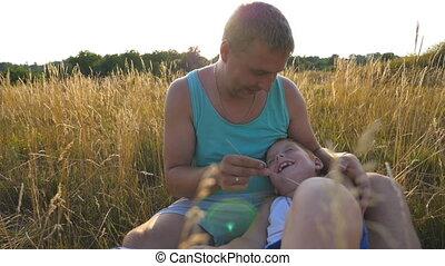 boy., zoon, vrolijk, afsluiten, weinig; niet zo(veel), vertragen, outdoor., vader, jonge, kieteldood, akker, vrolijke , zijn, zittende , kind, baby, man, papa, op, samen, hebben, motie, nature., plezier, gras, spelend