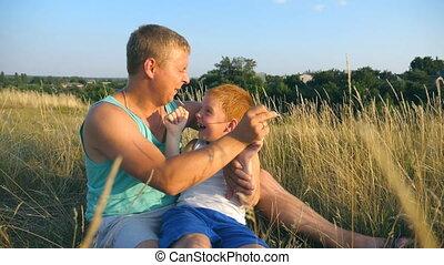 boy., zoon, vrolijk, afsluiten, weinig; niet zo(veel), vertragen, outdoor., vader, jonge, kieteldood, akker, vrolijke , zijn, kind, baby, man, papa, op, samen, spelend, motie, park., plezier, gras, hebben, het liggen