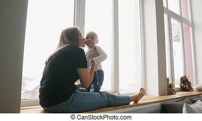 buitenkant., verfraaide, gezin, haar, het glimlachen., krans, jonge, zoon, het kijken, klesten, venster, zij, moeder, thuis, zittende , sill, kerstmis, vrolijke