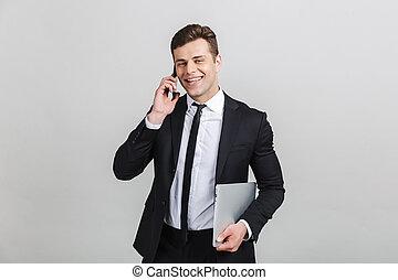 cellphone, beeld, jonge, klesten, terwijl, vasthouden, kostuum, zakenman, het glimlachen, draagbare computer, formeel