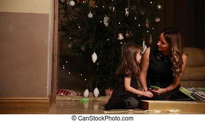 dochter, cadeau, zittende , onder, boompje, mamma, gifts., meisje, het untying, open, kerstmis, lint
