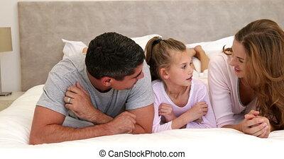 dochter, ouders, het liggen, kletsende, bed