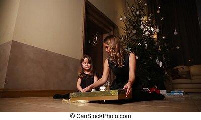 dochter, zittende , tuinbroek, onder, boompje, gift., plan, mamma, gifts., meisje, het untying, open, kerstmis, lint