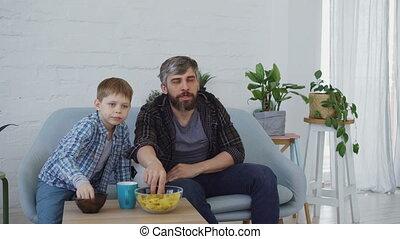 geconcentreerd, weinig; niet zo(veel), voetbal, eten, gezin, het schouwen tv, concept., vader, juichen, zoon, hoog, vieren, vijf, overwinning, lucifer, sportende, snacks., thuis, vrolijke