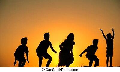 geitjes, silhouette, samen, springt, vijf, ondergaande zon