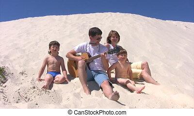 gezin, mondharmonica, het zingen, gitaar, zit, strand