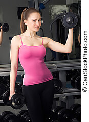 glimlachende vrouw, barbells, fitness