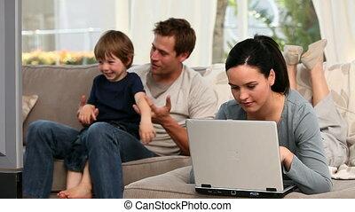 haar, draagbare computer, echtgenoot, terwijl, schouwend, gebruik, jongen, tv, vrouw