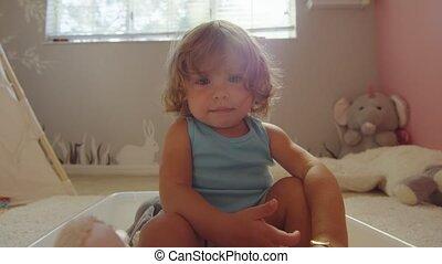 het glimlachen, het kijken, klein meisje, haar, zittende , fototoestel, terwijl, kamer, naar