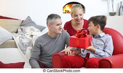 het glimlachen, kamer, gezin, zittende , openhaard, vrolijke , hun, kind, levend, getrooste, thuis, geven, blij, vrolijk, cadeau, ouders, kerstmis