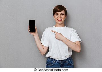 het glimlachen, wijzende, vrouw, aantrekkelijk, jonge, cellphone, vinger, beeld