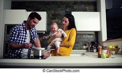 het voeden, haar., gezin, jonge vrouw , vasthoudende baby, thuis, man