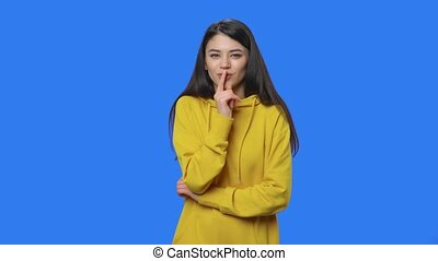 jonge, sweatshirt, stilte, achtergrond., het poseren, gereed, verticaal, 59.94fps., blauwe , vertragen, boven., dan, iets, secret., scherm, gele, over, brunette, afsluiten, gebaar, klesten, vervaardiging, vrouw, studio, motie