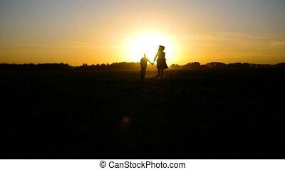 jongen lopend, ondergaande zon , meisje
