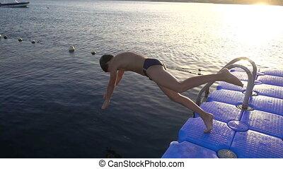 jongen, silhouette, springt, ondergaande zon , zee, pijler