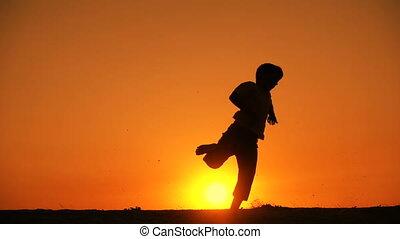 jongen, springt, silhouette, ondergaande zon