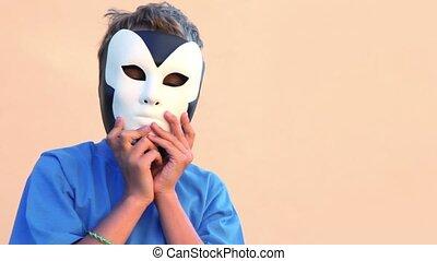 jongen, weinig; niet zo(veel), dan, houden, verwijdert, twee, maskers, een, hen, een ander, gezichten