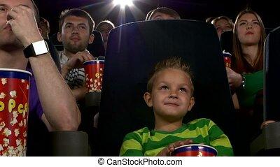 jongen, weinig; niet zo(veel), eten, bioscoop, film, schouwend, popcorn