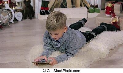 jongen, weinig; niet zo(veel), milieu, kamer, display, vloer, gebruiken, boompje, digitale , witte , openhaard, kerstmis, het liggen