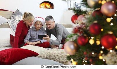 kamer, familie huis, vrolijk, beweeglijk, het glimlachen, zittende , openhaard, ouders, blik, vrolijke , getrooste, verlicht, boompje, blij, kerstmis, verfraaide, hun, zoon, telefoon, levend