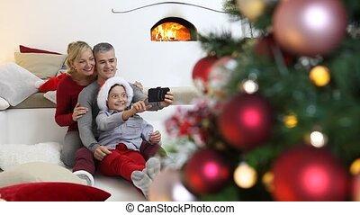 kamer, familie huis, vrolijk, beweeglijk, het glimlachen, zittende , openhaard, ouders, selfie, vrolijke , getrooste, verlicht, boompje, blij, kerstmis, nemen, verfraaide, zoon, telefoon, levend
