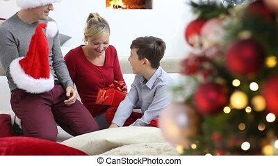 kamer, familie huis, vrolijk, cadeau, het glimlachen, zittende , openhaard, geven, ouders, vrolijke , getrooste, verlicht, boompje, blij, kerstmis, verfraaide, hun, kind, levend