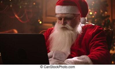 kerstman, moderne, zittende , werkende , terwijl, vrolijk, openhaard, stoel, het glimlachen, claus., achtergrond., draagbare computer, boompje, claus, zijn, kerstmis
