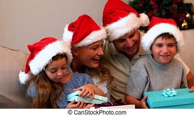 kerstmis, het openen stelt voor, jonge familie, vrolijke
