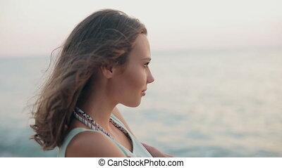 kijkende vrouw, ondergaande zon , zee, nieuwsgierig, genoegen