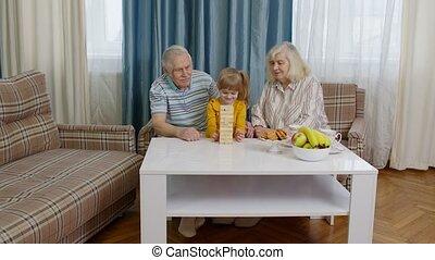 kind, spel, spelend, senior koppel, grootouders, blokjes, geitje, thuis, houten, kleindochter