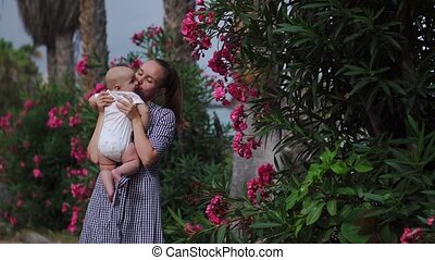 kind, toneelstukken, ongeveer, gezin, kussen, moeder, resort., bomen, palm, omhelzingen, baby, bloemen, vrolijke