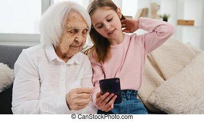 kleindochter, smartphone, grootmoeder