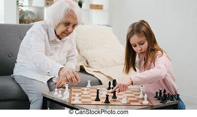 kleindochter, spelend, grootmoeder, schaakspel