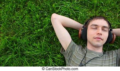 mannen, jonge, koptelefoon, gras, muziek, panning, groene, het liggen, luisteren